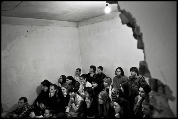The audience inside the 'house-theatre' listening a reading from a student of Belarus Free Theatre, taken in 2009 by photographer Alessandro Vincenzi. The audience was contacted by the company in a private and secret way the day before or the same day of the performance in Minsk, Belarus.