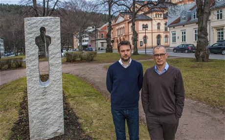 David Greig (left) and director Ramin Gray standing beside a memorial to three teenage victims of the Anders Breivik massacre, with the Drammens Teater in the background